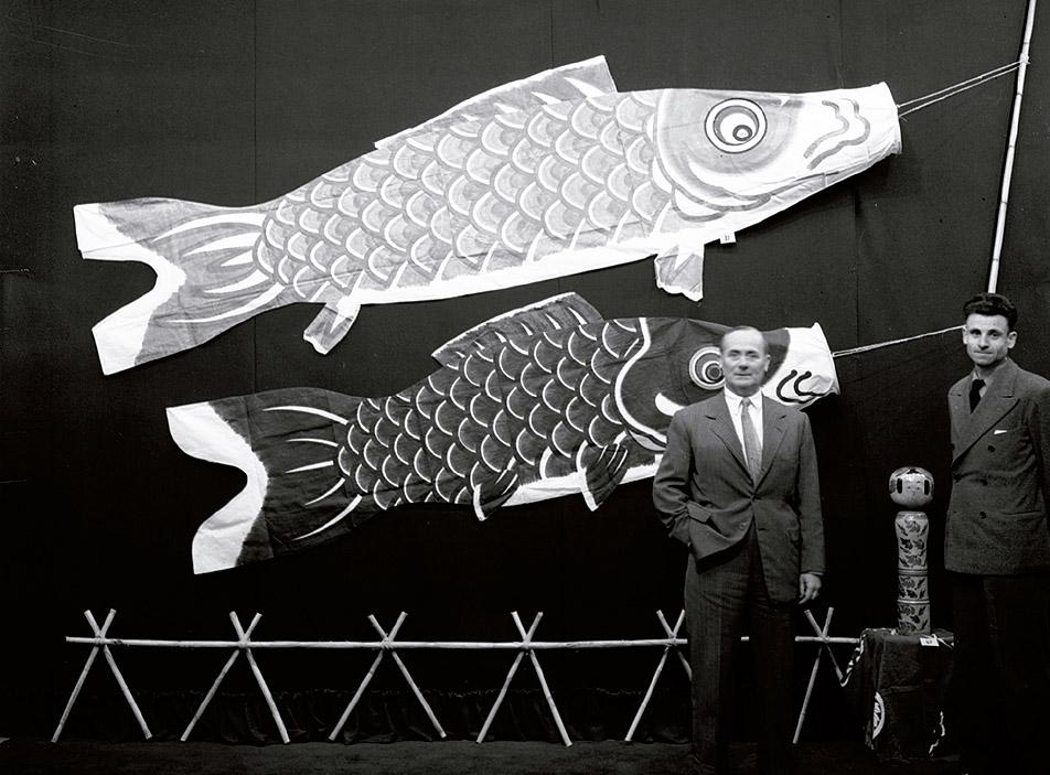 Joan Miró y Eudald Serra en la exposición de arte popular japonés, fotografiados con una kokeshi y dos carpas koinobori de la colección de Cels Gomis. Fotografía de Joaquim Gomis, 1950. Colección particular.