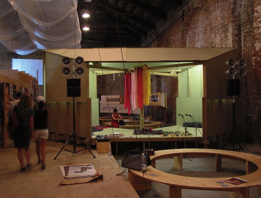 Interior de la Utopia Station. La estructura de madera, con los bancos circulares y el escenario, ha sido diseñada por los artistas Liam Gillick y Rirkrit Tiravanija. © Archivo de la Bienal de Venecia.