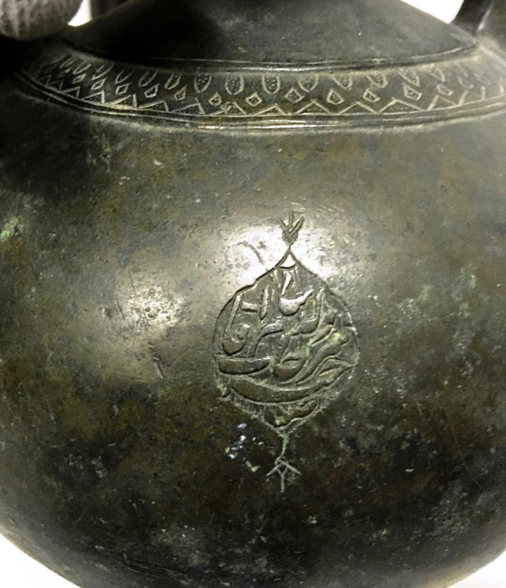 "Detalle con la inscripción en persa: ""Sāhib-e Sorḵāb Valad-e Sām āqā""."