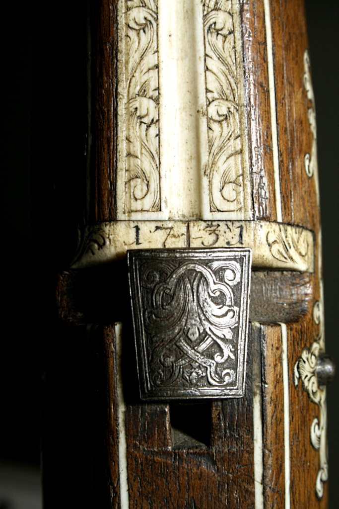 Detalle de la placa de hueso con la fecha 1731 y la nuez de la ballesta de caza